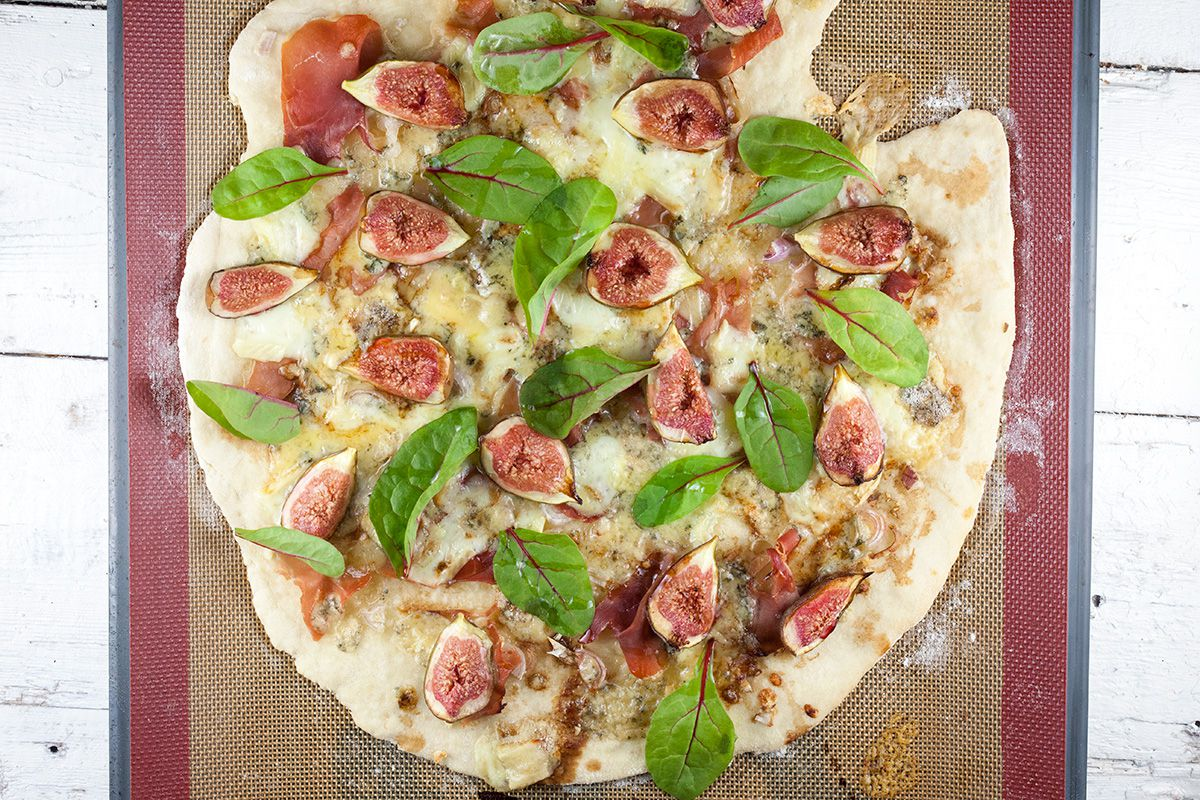 Fig-prosciutto pizza with purple baby spinach